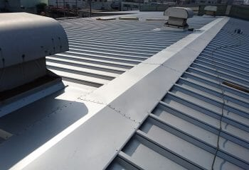 投稿を編集       下書き保存 プレビュー 公開   タイトルを追加 横浜市の折板屋根カバー工法はテイガクで 共通メタデータ  メタタイトル 横浜市の折板屋根カバー工法はテイガク屋根修理で - テイガク屋根修理 メタディスクリプション 横浜市で折板屋根のカバー工法を行う業者をお探しのお客様はテイガク屋根修理にお問い合わせください。弊社は屋根工事専門の工事会社です。適切なリフォーム工事をご提案させていただきます。 メタキーワード 屋根の修理, リフォーム, 横浜市 単語と単語は「,」で区切って入力してください  施工例メタデータ  施工実施年月(例:2021年01月) 2016年8月 施工地域(例:東京都世田谷区) 神奈川県横浜市 お施主様(例:A様邸) K様邸 工事種別(例:屋根カバー工法) 折板屋根のカバー工法(重ね葺き) 横浜市で折板屋根のカバー工法を行う業者をお探しのお客様はテイガクにお問い合わせください。弊社は屋根工事専門の工事会社です。適切なリフォーム工事をご提案させていただきます。  神奈川県横浜市で施工したカバー工法リフォーム BEFORE 横浜市で雨漏りが発生している工場屋根の改修工事 横浜市で製造工場を経営しているオーナー様からお問い合わせをいただきました。 お問い合わせ内容は雨漏りが発生している工場の改修工事についてでした。 横浜市は全国で最もお問い合わせが多く、施工実績も豊富な地域です。 横浜市の屋根修理・リフォーム事例一覧はこちら 対象の工場は大規模建築物にあたり、屋根の平米数は2000を超えます。 既存で使用している屋根は折板屋根で、建築後約35年が経過しています。 雨漏りの被害に悩まされており、既存の屋根には他の業者が簡単な応急処置を行っていました。 応急処置だけでは雨漏りを改善することが困難であるため、根本的な改修工事を行うことになりました。 およそ、半年にわたる工事計画と価格交渉が続き、最終的にテイガクで改修工事を請け負わせていただきました。 テイガクホームページでは主に住宅のリフォーム工事をご案内していますが、今回の事例のように工場の大規模改修工事も承っております。 適切価格かつ高い品質の工事をお求めの工場や倉庫のオーナー様がいらっしゃれば、テイガクに一度、お問い合わせください。 もちろん、お見積りは無料です。   横浜市の工場屋根改修工事 事前調査 横浜市の工場屋根改修工事 事前調査 横浜市鶴見区のお客様かあお問い合わせいただきました。 東京湾沿いにある大規模な工場屋根です。 屋根の劣化が進行しており、雨漏りがところどころ発生しています。 他の業者様がブルーシートと土嚢(ドノウ)をお置いて、雨漏りを防ぐ応急処置をしたようです。 しかし、屋根にブルーシートを被せることは、十分な応急処置とは言えません。 台風や強風で簡単にシートはめくれ上がり、すぐに雨漏りを発生させてしまいます。 雨漏りは工場内の備品や商品に損害を与え、工場の生産性も低下させます。  横浜市の工場 雨漏り応急処置 横浜市の工場 雨漏り応急処置 ブルーシートで屋根を覆い、雨漏りの発生を防いでいますが、ドノウ袋が破れてしまい屋根が砂だらけになっています。 ドノウを重みに使用する処置は、海岸沿いでは風が強いため、すぐにこのような状態になります。 この状況ではブルーシートを被せ直すことが困難です。 ドノウを屋根の上に置くことはできる限り、控えてください。  横浜市の折板屋根工事開始  工場の屋根工事は工期や工事方法、工事値段の交渉でかなりの時間を費やします。 また、夏の台風や冬の大雪などの影響も考慮する必要があります。 オーナー様からは今年の1月にお問い合わせをいただき、2016年の台風シーズン前までの完工のご意向もいただきました。 長期的で計画性のある改修工事が求められます。 もちろん、工事のスケジュール管理はテイガクの現場監督にお任せ下さい。  折板屋根のカバー工法金具 折板屋根のカバー工法金具 横浜市の折板屋根工事、開始です。 既存の屋根の上に新しい折板屋根を重ねて張るカバー工法で改修することになりました。 画像はカバー工法用の受け金具です。 折板屋根のカバー工法には2パターンあります。 ひとつは、防水シートを張る方法、もうひとつは、新しい折板屋根を重ね張りする方法です。 屋根の損害が大きい場合(雨漏りがいたるところで発生している場合)は後者の新しい折板屋根を重ね張りする方法を採用します。 今回は屋根の劣化が著しく進行しているたため、カバー工法による改修工事をいたします。  折板屋根の制作  今回の横浜市の現場はかなり大規模な工場であるため、トラックで既製品の屋根材を運搬することができません。 そのような条件の場合は、既存の屋
