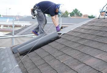 ルーフィングを屋根に施工中
